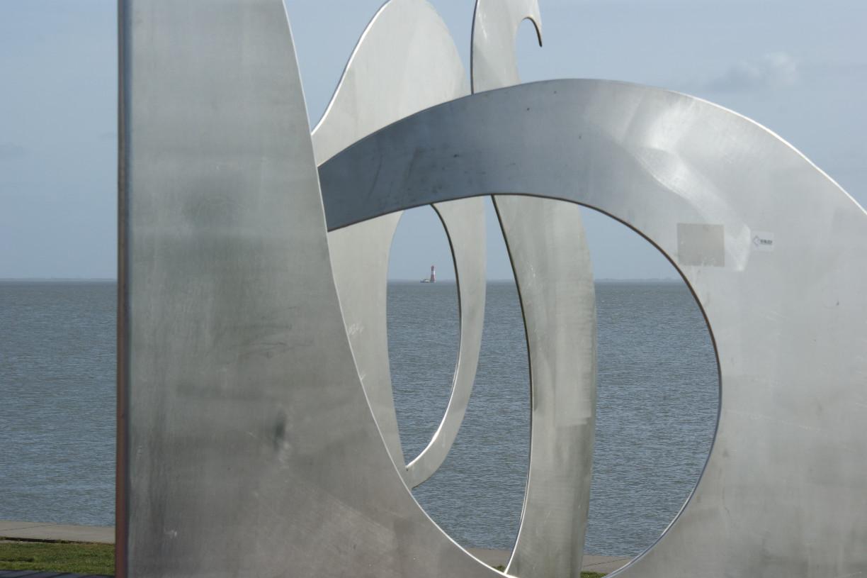 """Blick durch die Skulptur """"Welle über die Mauer"""" auf den Leuchtturm Arngast © Barbara"""