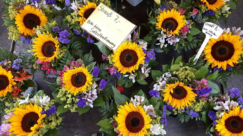 Ein Stand voller gebundener, gelb leuchtender Sonnenblumensträuße