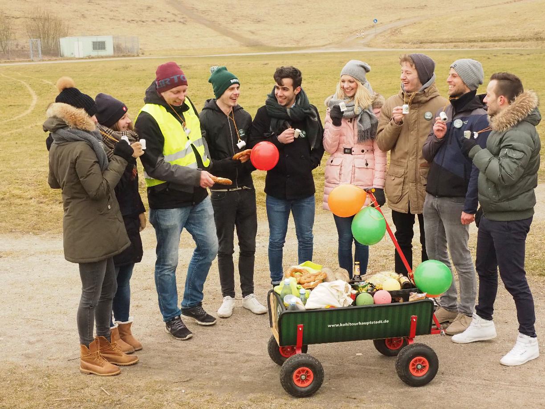 Eine Gruppe Menschen (Teilnehmer der Kohlfahrt) stehen um einen gefüllten Bollerwagen.