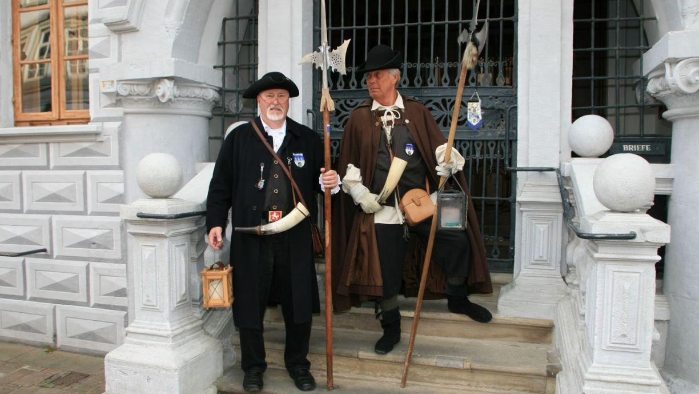 Die Celler Nachtwächter stehen vor dem Alten Rathaus.