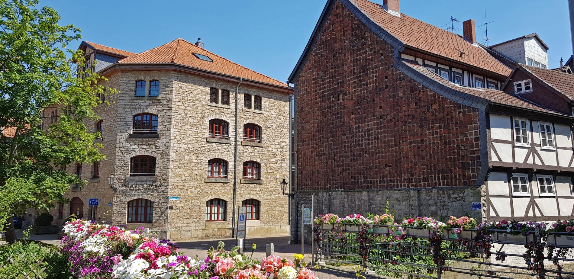 Links das Bankhaus Seeliger von hinten, rechts ein Fachwerkhaus, im Vordergrund Blumen