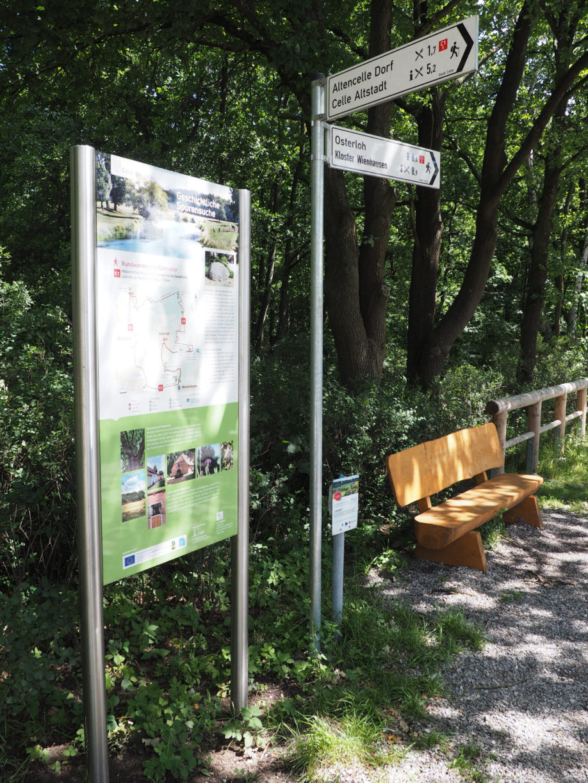 Eine Infotafel mit Sitzbank am Startpunkt des Wanderwegs.