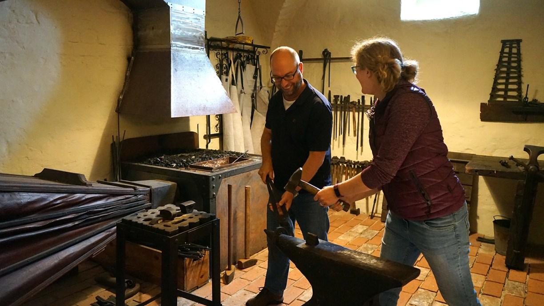 Dr. Florian Westphal und Christine Fabian mit Hammer und Zange in der historischen Schwarzschmiede der Museumsburg Brome