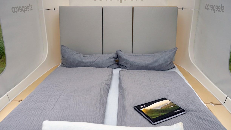 Das Innere des Sleeperoo-Schlafwürfels mit Bettdecken und Kissen