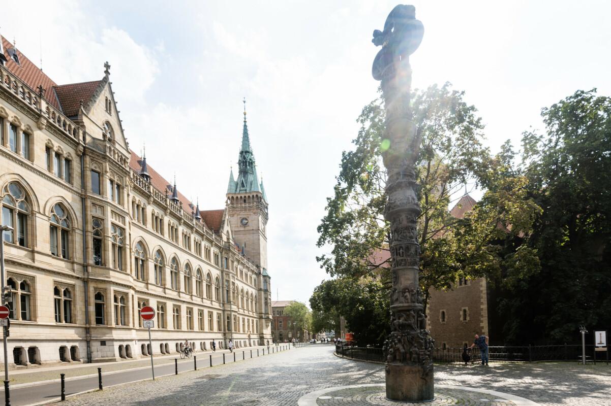 Ungewöhnliche Straßennamen und die Geschichten dahinter: Im Vordergrund eine Säule, dahinter grüne Bäume, zwischen denen der Dom durchschimmert. Links im Bild das Rathaus Braunschweig.