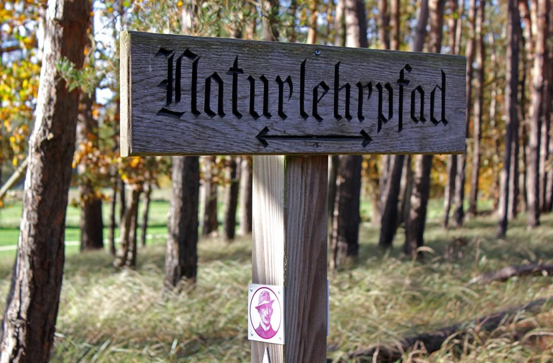 Holzschild mit Hinweis zum Naturlehrpfad und Hermann-Löns-Plakette