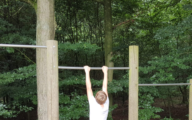 Ein Jugendlicher hangelt an der mittleren von 3 unterschiedlich hoch angebrachten Stangen, die ebenfalls am Trimm-dich-Pfad gegenüber der Calisthenics-Station aufgebaut sind.