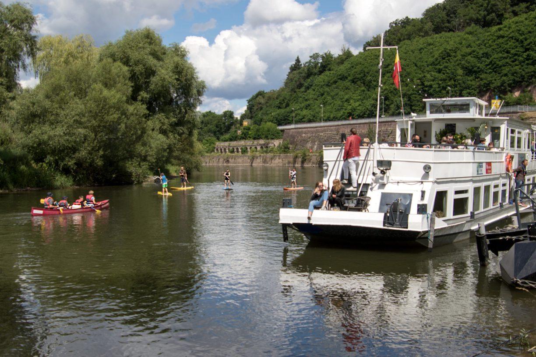 Wasserwanderung in Hann. Münden: Das Schiff MS Weserstein auf der Weser umgeben von Kanuten und Stand Up Paddkern.