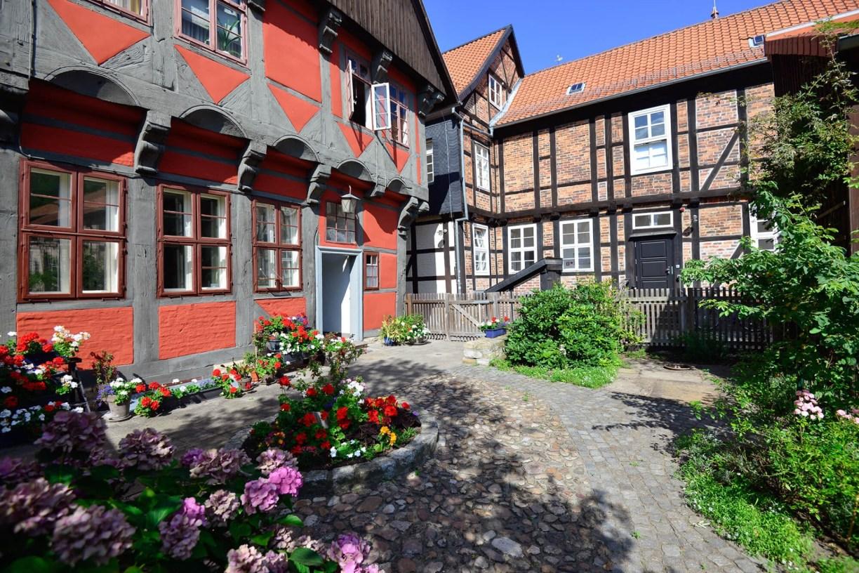 Innenhof des Kavalierhauses mit rot-grauem Fachwerk mit Garten in der Gifhorner Altstadt