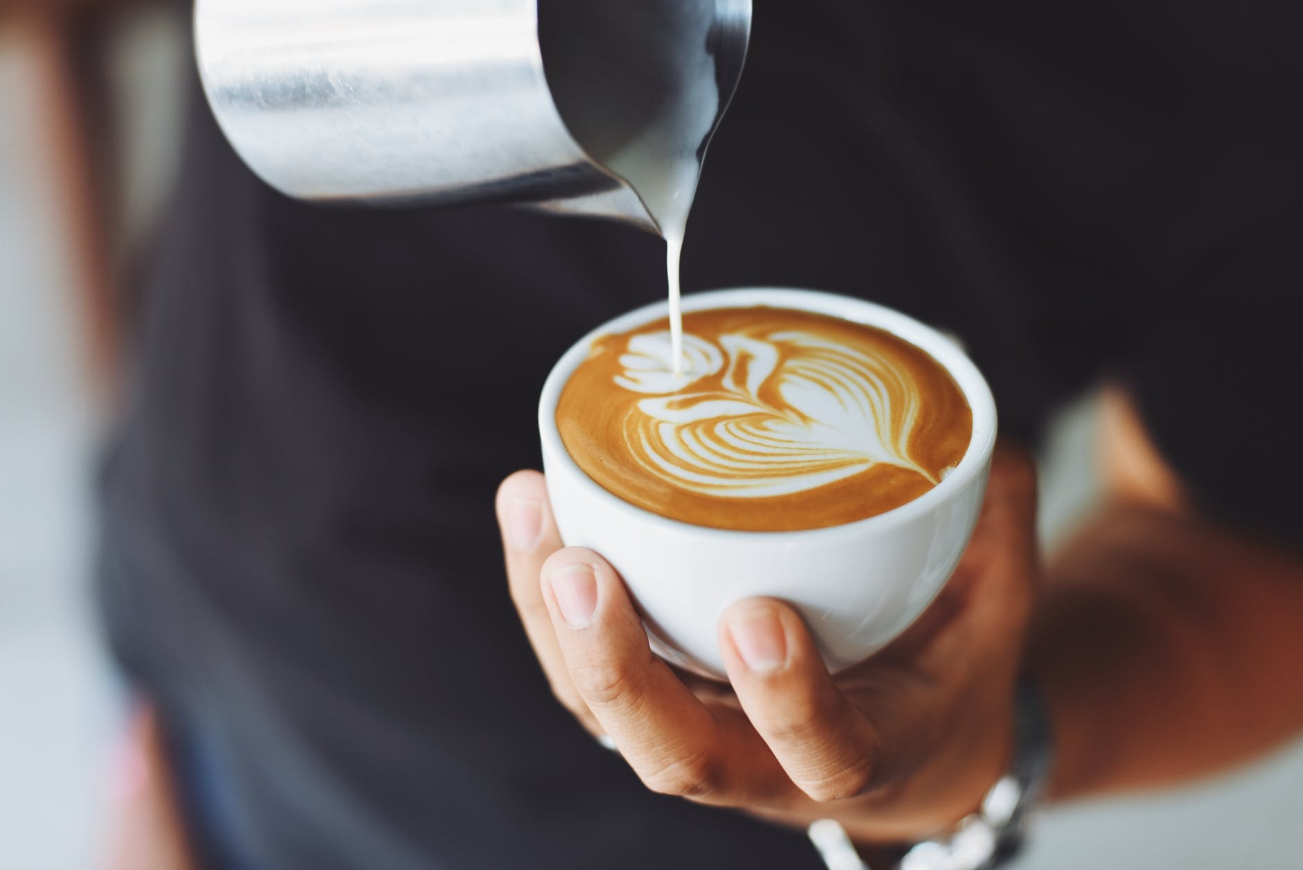 Man holding a coffee cup while making latte art
