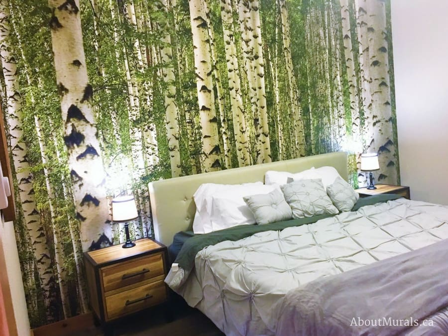 Birch wallpaper in green pattern in a bedroom with a bed and wooden tables from AboutMurals.ca