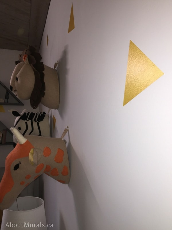 A shimmery triangle painted by Adrienne of AboutMurals.ca on the walls of a baby nursery, along with stuffed animal heads.