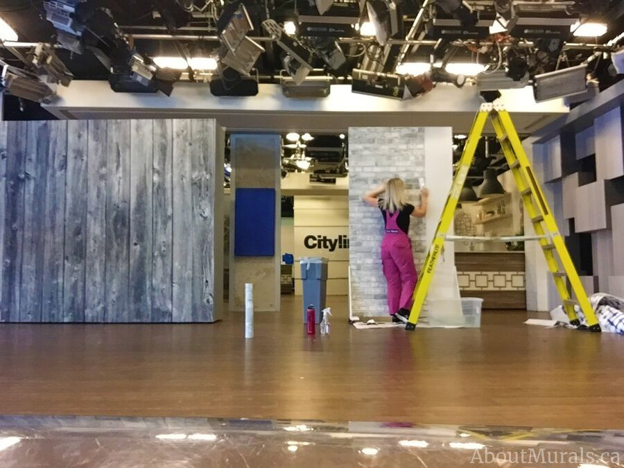 Adrienne of AboutMurals.ca hangs a removable brick wallpaper on set at Cityline