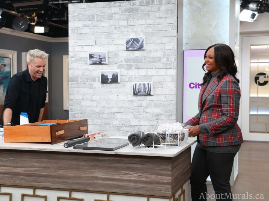 Christian Dare and Tracy Moore stand in front of a removable brick wallpaper from AboutMurals.ca on set at Cityline