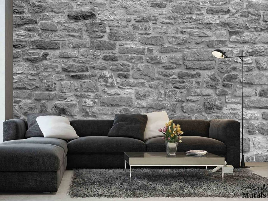 Grey Stone Wallpaper, as seen on the wall of this living room, features a textured, 3D looking stacked stone wall. Stone wall murals sold by AboutMurals.ca.