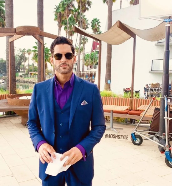 Tom Ellis on the set of Lucifer Season 6 in a purple suit and wearing aviator style sunglasses, holding a paper.