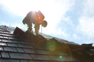 Roofer silhouette while installing shilngles on roof