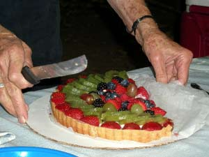 cutting the fruit tart for dessert