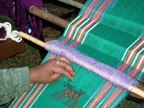 A backstrap weaver picks up an intricate design