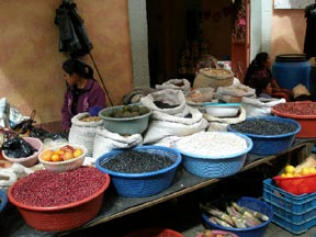 A vendor displays many colored beans at a stall in the marketplace