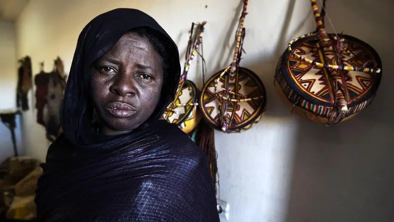 "A Tuareg woman who is an imzad instrument maker poses for a picture at the ""Home of the Imzad"" in Tamanrasset in Southern Algeria, on January 12, 2016. The imzad, single-stringed violin played only by Tuareg women, is making a comeback in Algeria as the last of its players come to the rescue of a tradition on the verge of extinction.    / AFP / Farouk Batiche"