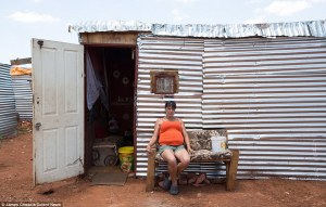 A woman sits outside her makeshift home in the squatter camp in Munsieville, a township in the Krugersdorp area in Gauteng Province