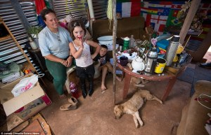 A family pose for the camera inside their makeshift shelter - houses are typically built with bare earth floors, but floods wash away the top soil and leave decades-old waste exposed