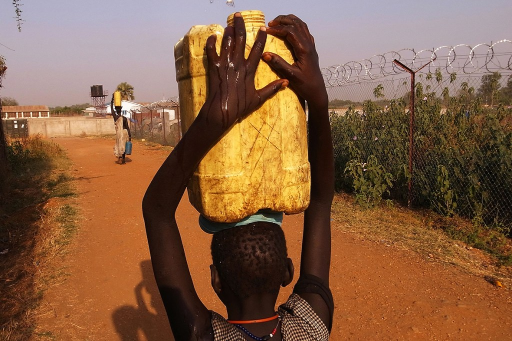 11 January, 2011: A girl carries water back to her home in an area for displaced Sudanese in the southern Sudanese city of Juba, SudanSpencer Platt/Getty Images