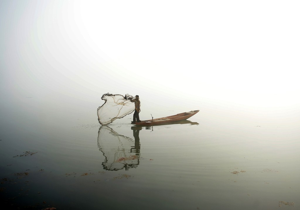 13 January, 2016: A Kashmiri fisherman throws out his net from his boat on Dal lake during dense fog in SrinagarTauseef Mustafa/ AFP