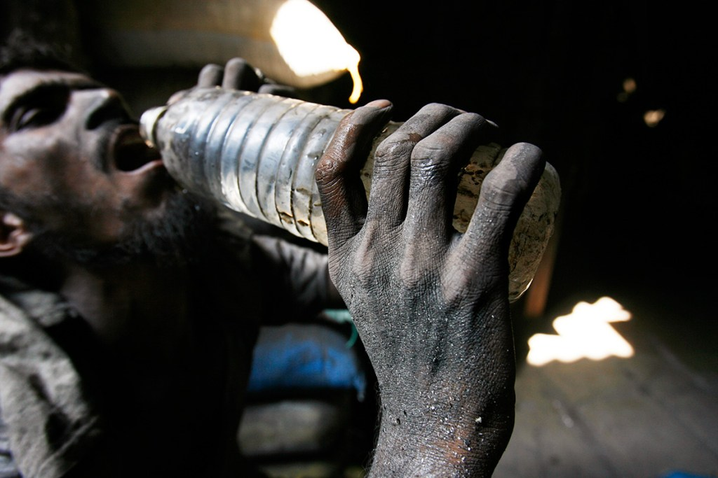 28 November 2007: An Indian labourer drinks water at an aluminium reprocessing unit in Dharavi, Asia's largest slums in MumbaiArko Datta/ Reuters