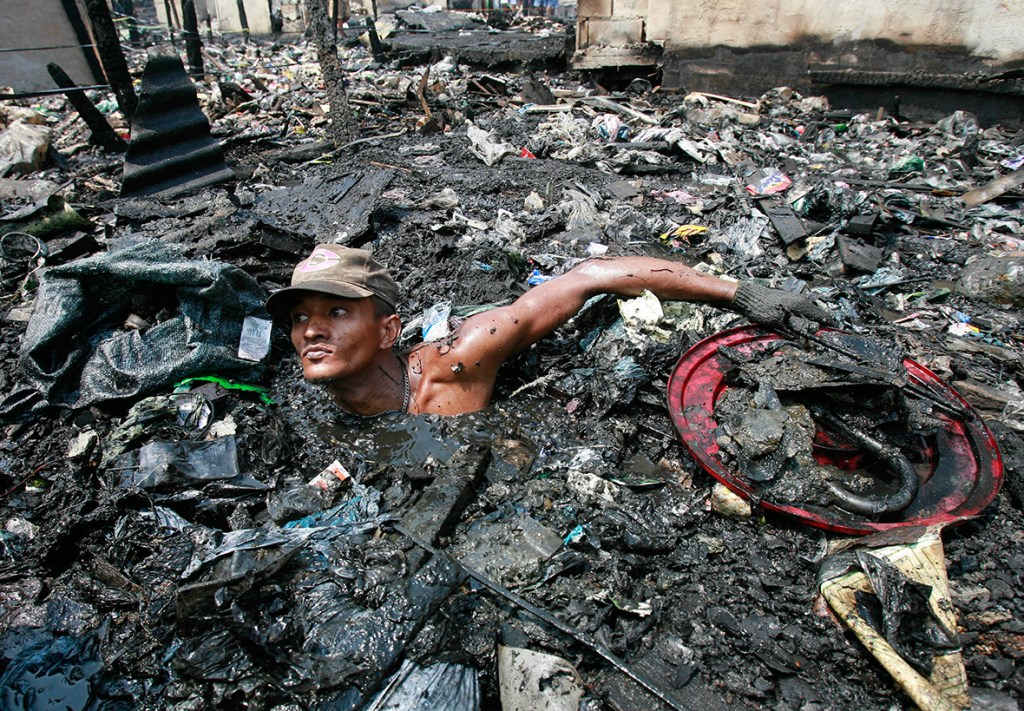 13 April 2007: A man searches through debris in polluted water looking for items to salvage after a fire in a slum in Malabon, north of ManilaDarren Whiteside/ Reuters
