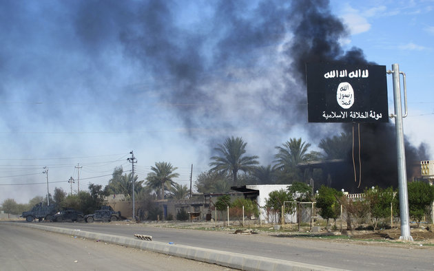 Smoke raises behind an Islamic State flag after Iraqi security forces and Shiite fighters took control of Saadiya in Diyala province from Islamist State militants,