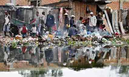 Residents walk past shanty houses along the Andriantany waste water channel in Madagascar's capital, Antananarivo. Photograph: Thomas Mukoya/Reuters