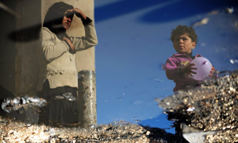 A Syrian internally displaced woman and child are reflected in a puddle of water in the Bab al-Hawa camp along the Turkish border in Idlib. Photograph: Bulent Kilic/AFP/Getty Images