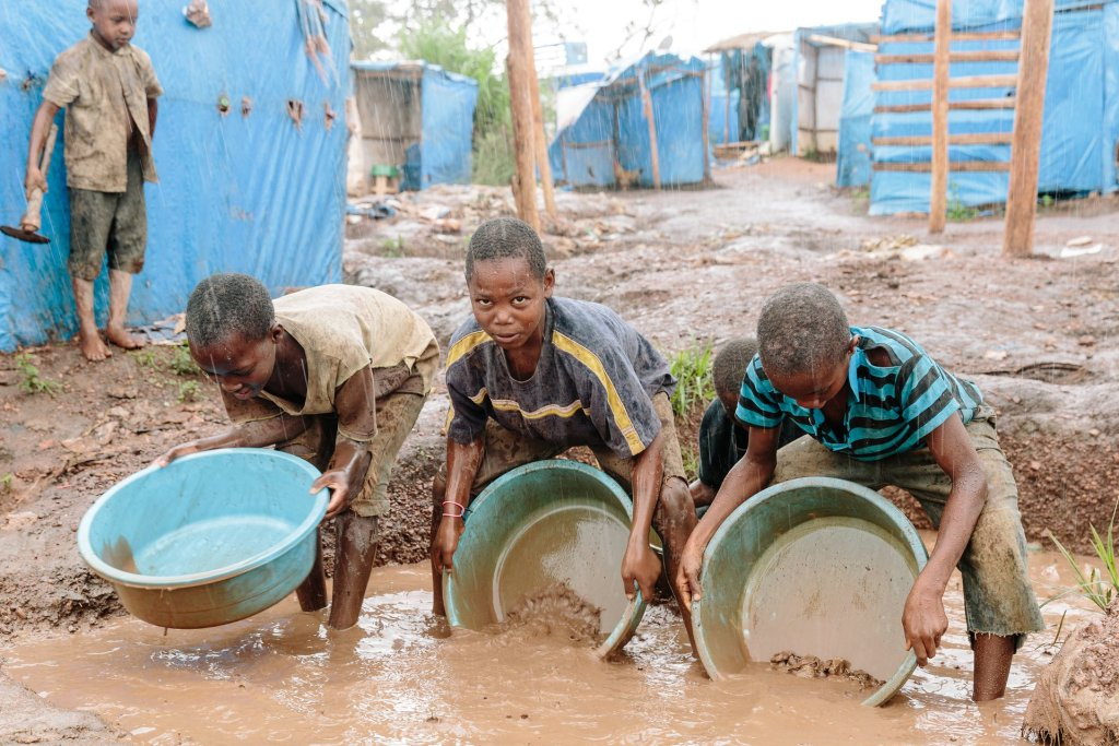 Using makeshift pans, children sluice gold ore while standing ankle deep in water. Photograph: Eelco Roos/Hivos