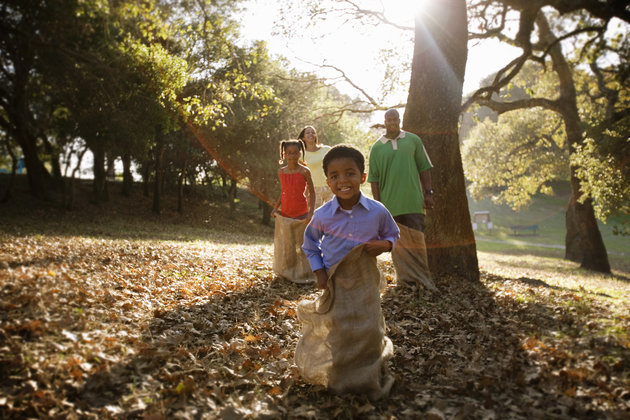 Young boy leads family in potato sack race in the park at sunset.