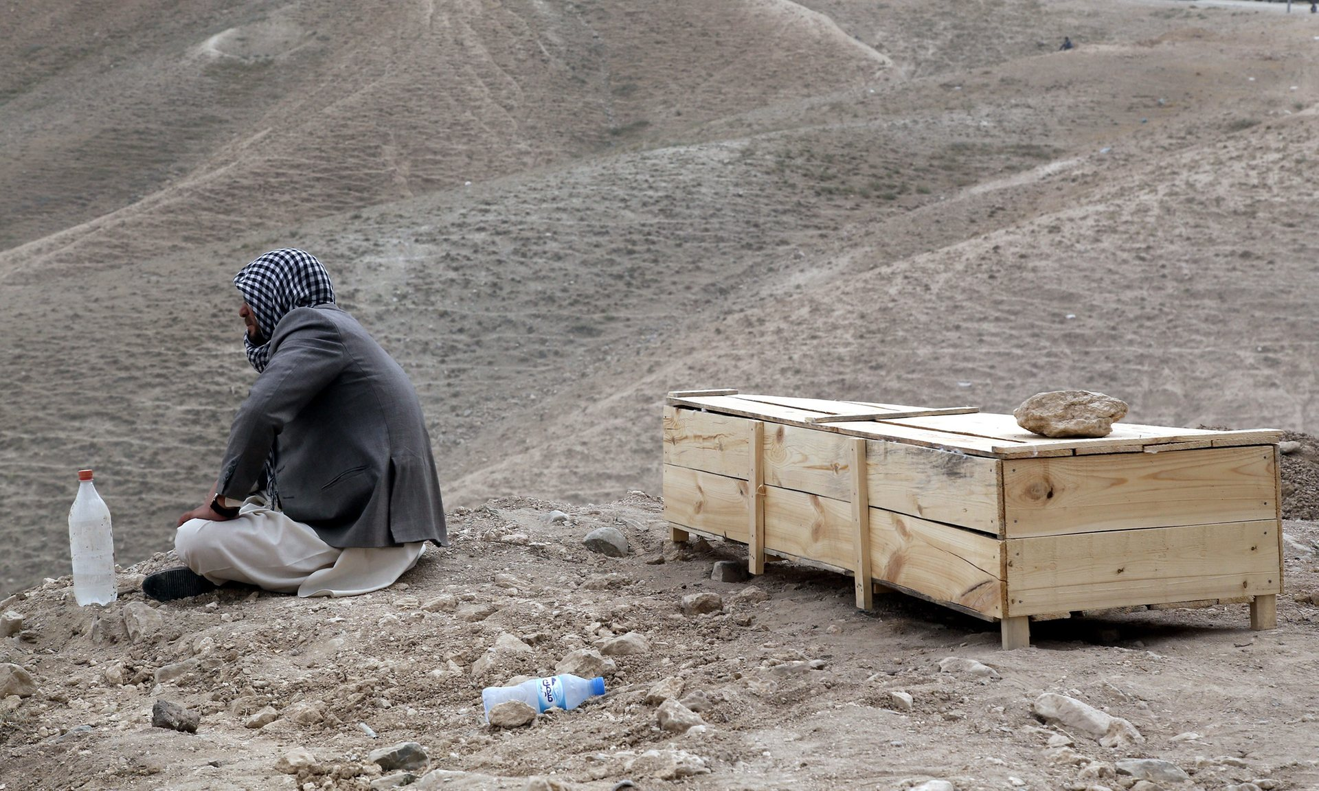 A man sits beside the coffin of his relative who was killed in a suicide bomb attack in Kabul, Afghanistan. Photograph: Jawad Jalali/EPA