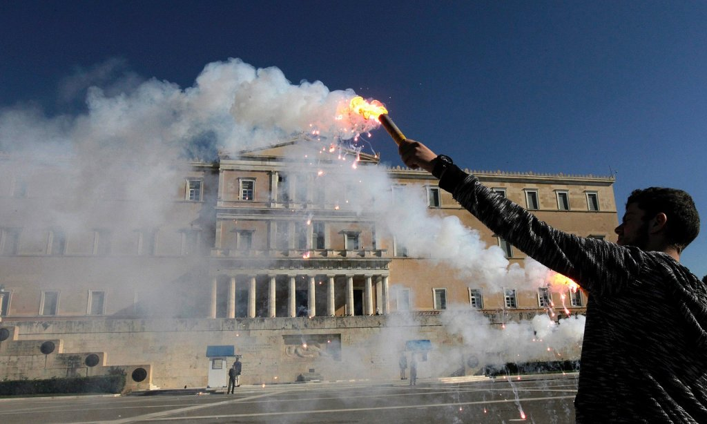 A student holds a flare in front of the Greek parliament building during an anti-austerity protest in Athens last November. The UK, Greece and Portugal were the only three OECD countries that saw real wages fall between 2007 and 2015. Photograph: EPA