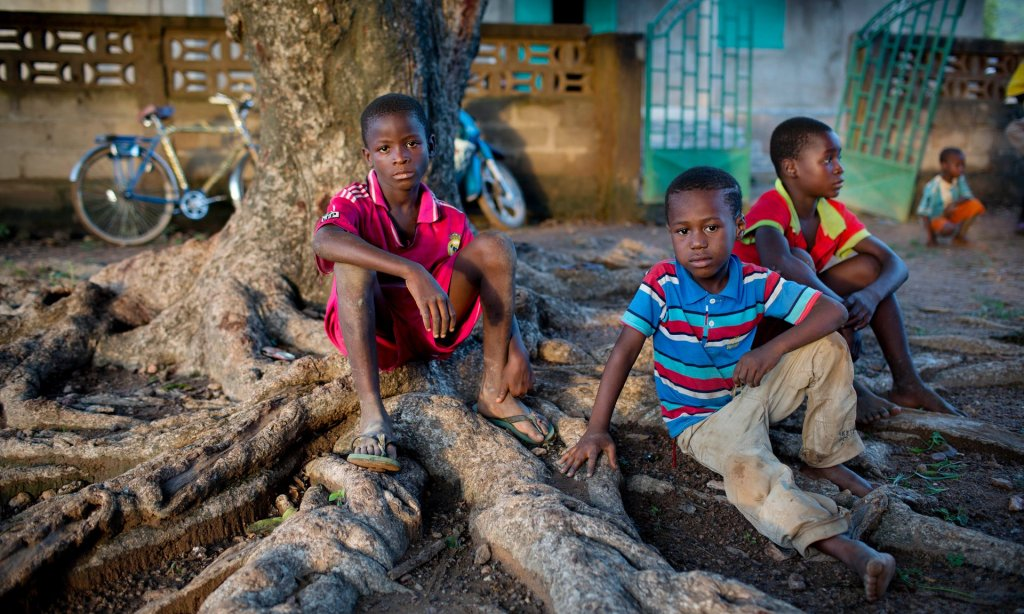 Children sit outside a clinic in a community near Doko, Siguiri, in northern Guinea. They have just been vaccinated for polio as part of a Unicef campaign backed by the Spanish government. Photograph: Kate Holt/Unicef