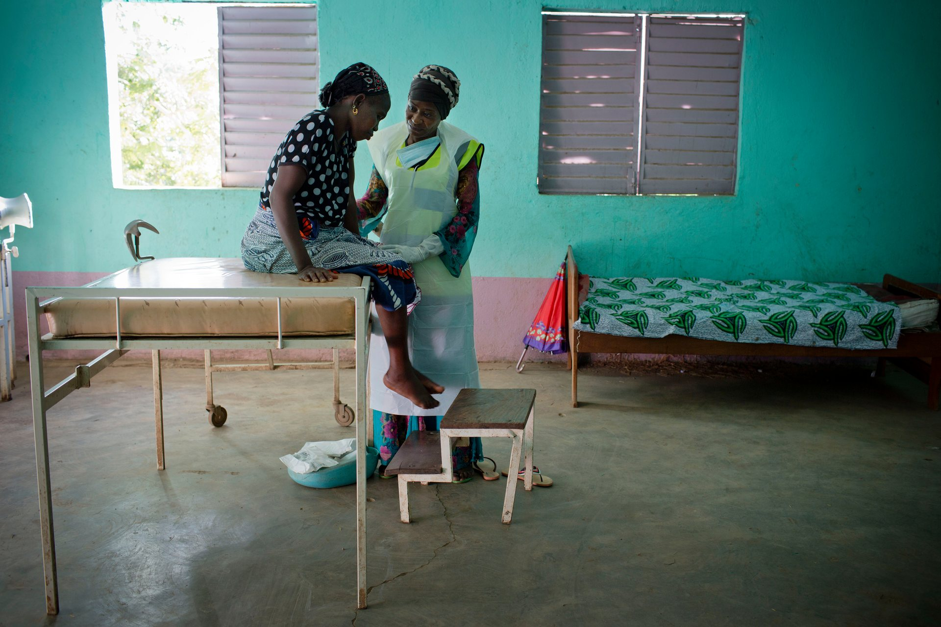 Sayon Keita, who is pregnant with her seventh child, is examined by a midwife at a health post near Doko, Siguiri