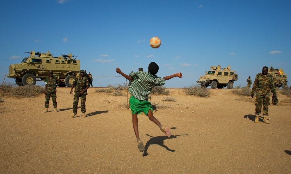 Ugandan soldiers deployed with Amisom play football with Somali children after taking back a town from al-Shabaab. Photograph: Irin