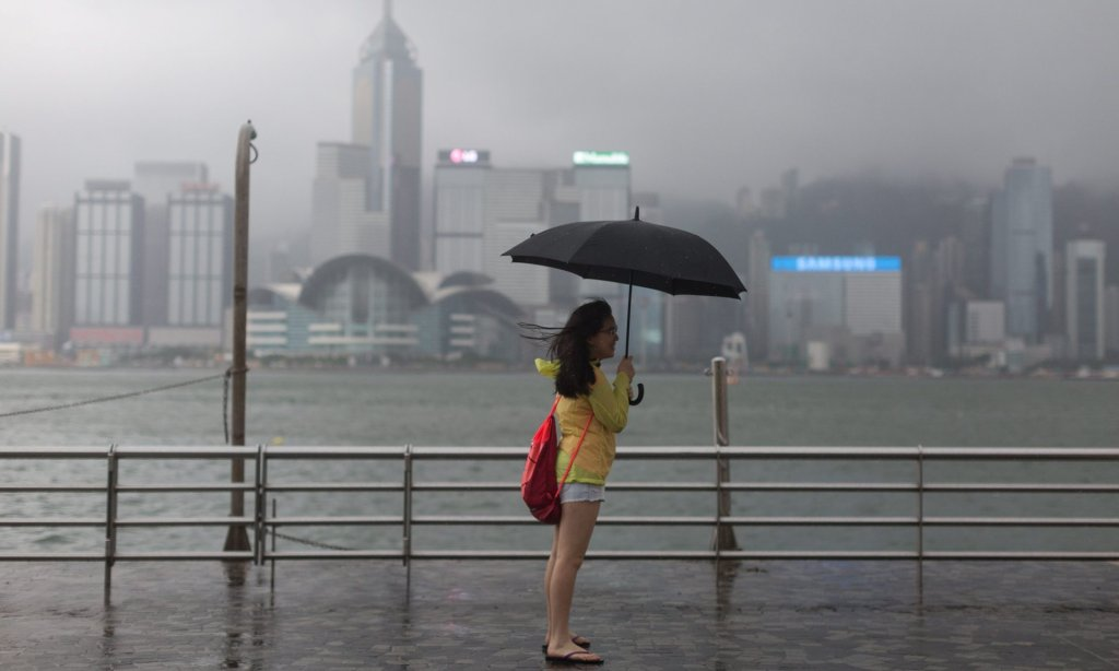 A woman stands on the Victoria Harbour waterfront during Typhoon Nida in Hong Kong. Photograph: Jerome Favre/EPA