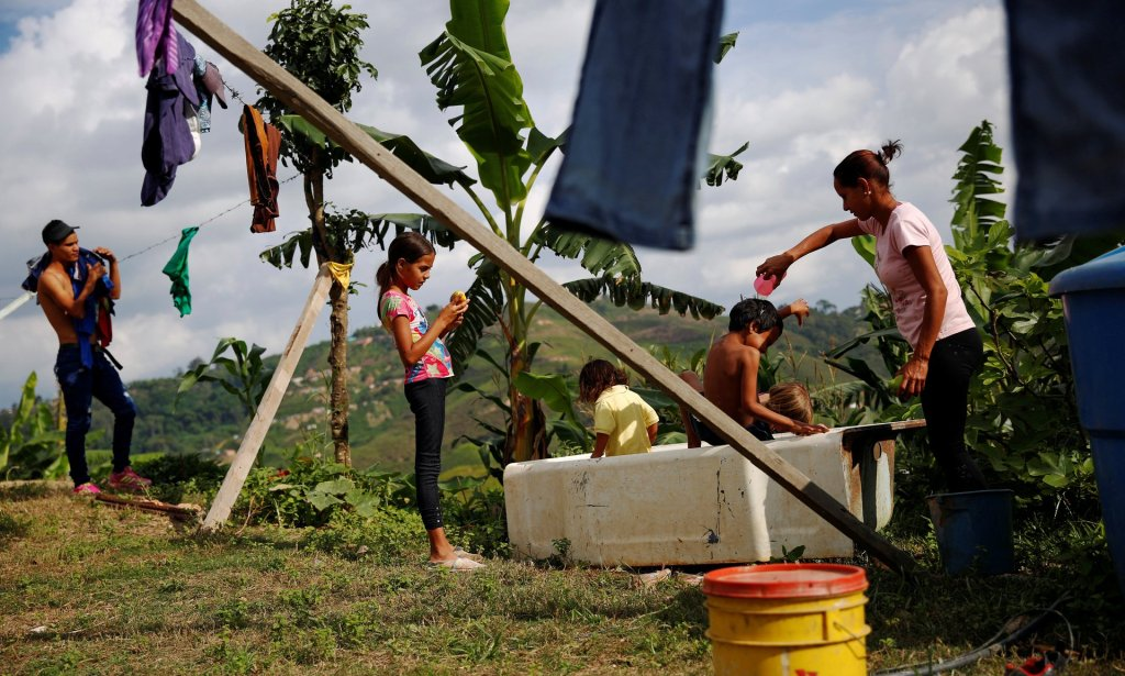 Lisibeht Martinez, right, 30, who was sterilized a year ago, plays with her children in a bathtub in the backyard of their house in Los Teques. Photograph: Carlos Garcia Rawlins/Reuters