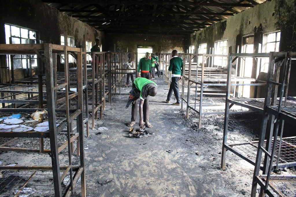Students of St Peter's Nyamesocho school in Kisii county rummage through a burnt-out dormitory for salvageable items following an arson attack. Photograph: AFP/Getty Images
