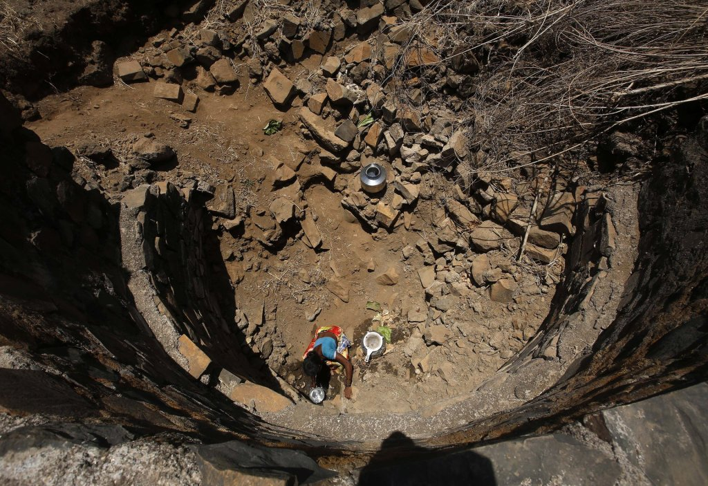 An Indian woman tries to collect water from a dried-up well in Maharashtra state. Across India, 76 million people lack access to safe water. Photograph: Rajanish Kakade/AP