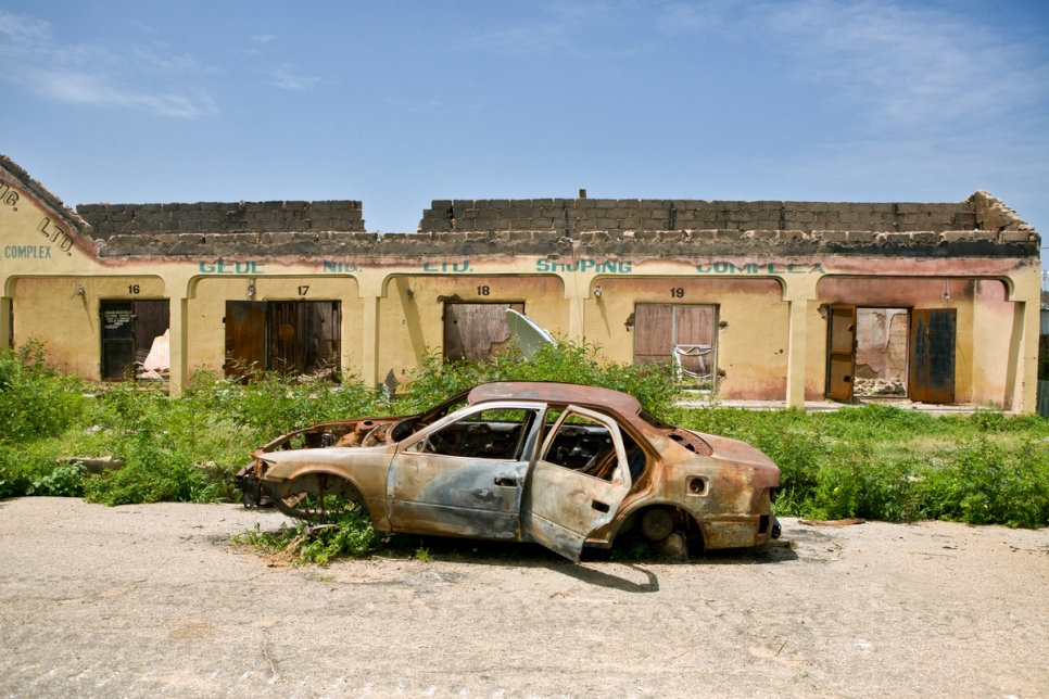 A burned out car lies in a street of destroyed homes in Gwoza, Nigeria, recently liberated by Nigerian armed forces. © UNHCR/Hélène Caux