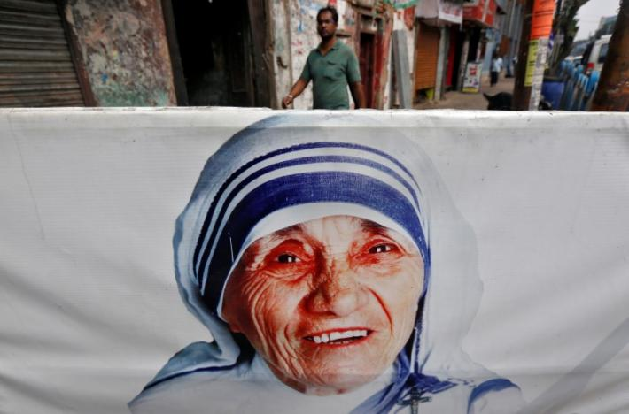 A man walks past a religious souvenir shop displaying a picture of Mother Teresa ahead of her canonisation ceremony, in Kolkata, India September 3, 2016. REUTERS/Rupak De Chowdhuri