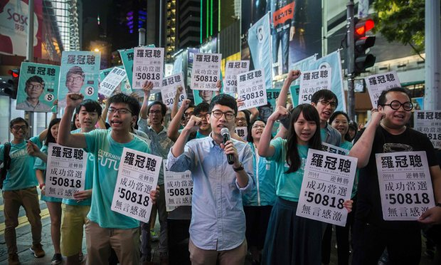 Nathan Law (centre) with Joshua Wong (centre-left) and supporters in Causeway Bay following Law's LegCo win. Photograph: Isaac Lawrence/AFP/Getty Images