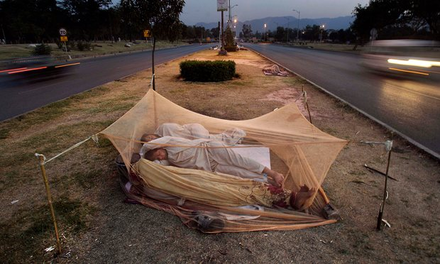 Pakistani labourers sleep under a mosquito net in the middle of a road in Islamabad. Photograph: Muhammed Muheisen/AP