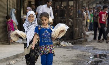 Syrian girls outside a bakery in a rebel-held neighbourhood in Aleppo, July 2016. The city has suffered enormous destruction in a war that has killed 400,000 across Syria, according to the UN. Photograph: Karam Al-Masri/AFP/Getty Images